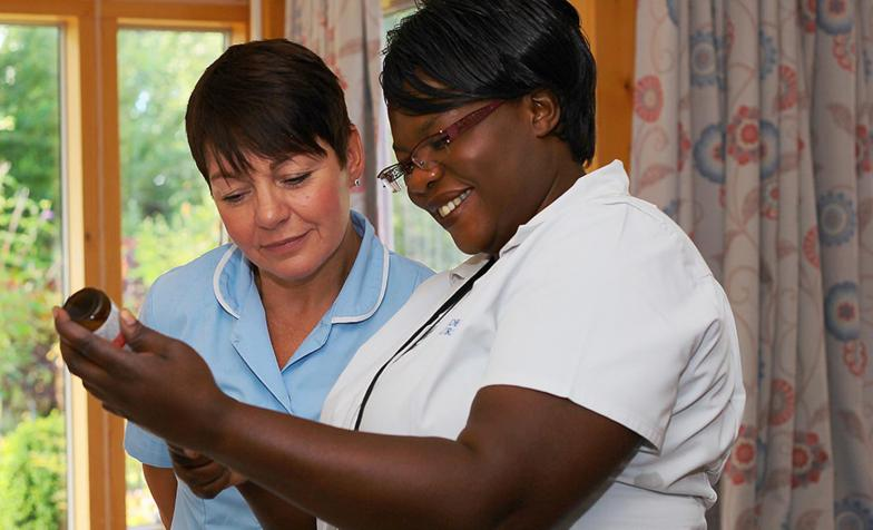 Two nurses looking at information on a bottle