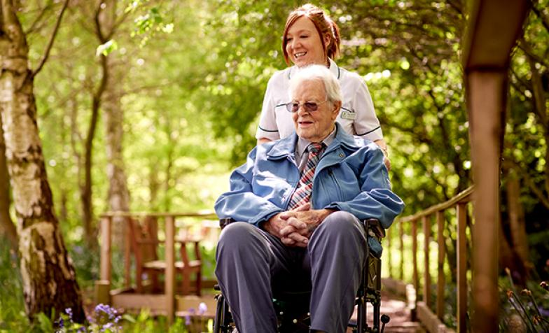 A hospice nurse with a patient in a wheelchair admiring the hospice gardens