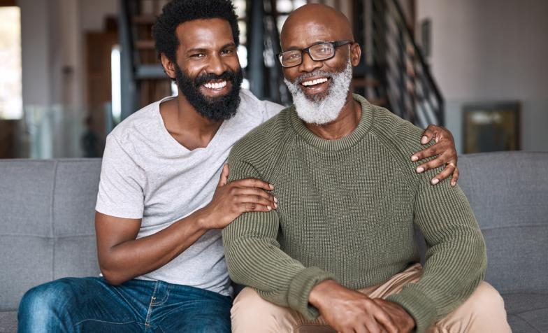 Portrait of a happy young man relaxing and spending time with his father at home