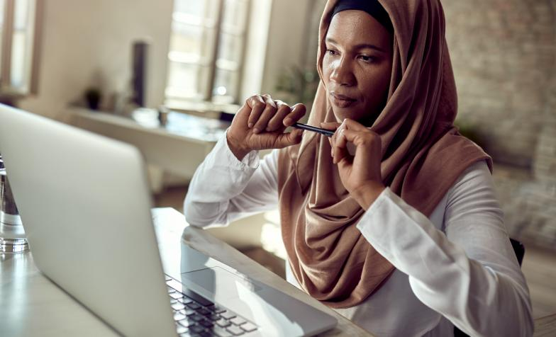 Woman wearing head scarf sitting at desk with laptop