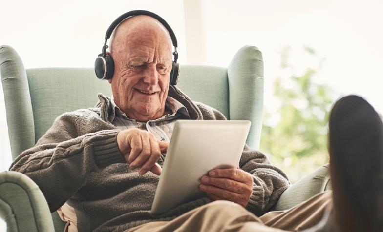 Older man watching film in tablet