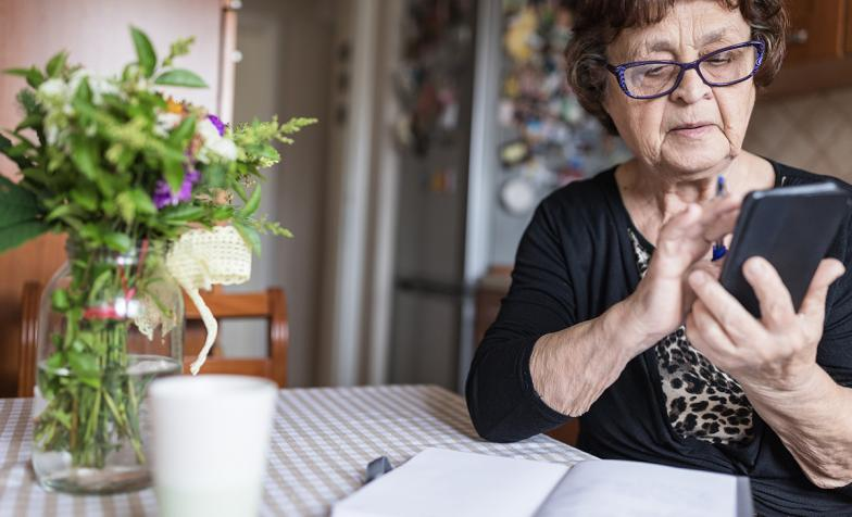 Older woman using smartphone with glasses on