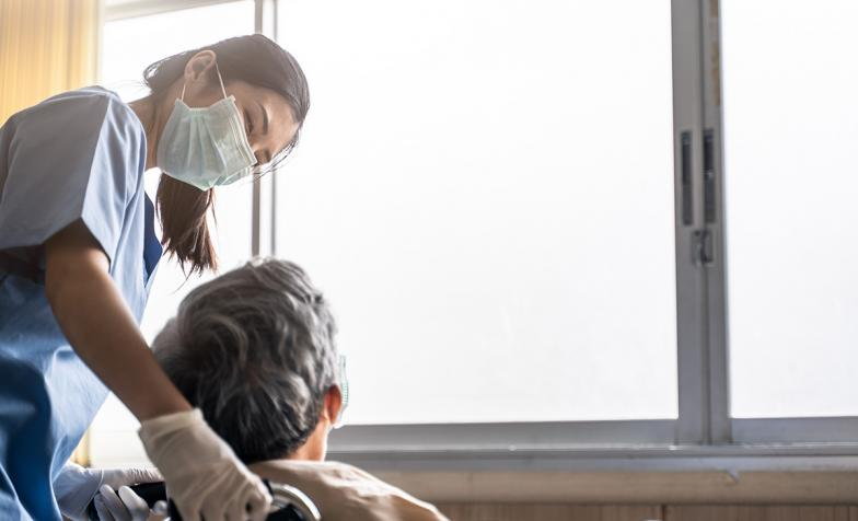 Nurse talking to patient in wheelchair