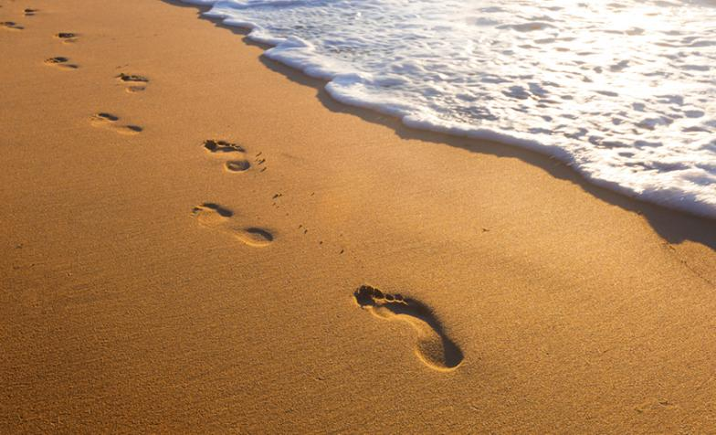 A stock photo of footsteps on a beach next to the sea