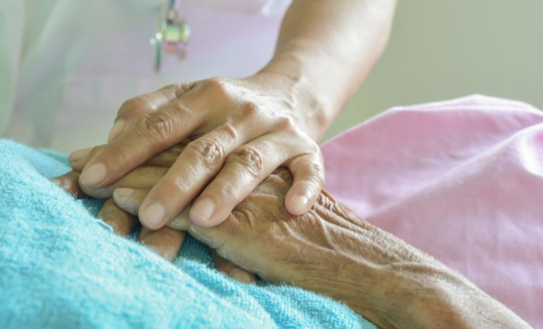 close up of holding hands on a bed