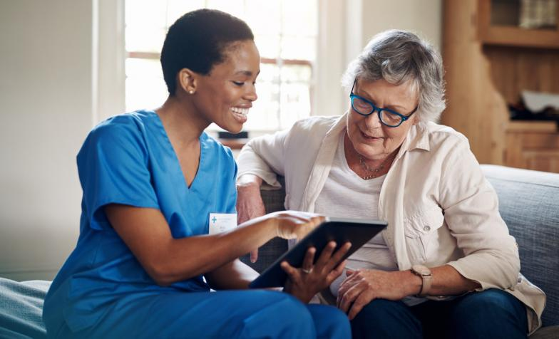 Carer with ipad and older woman