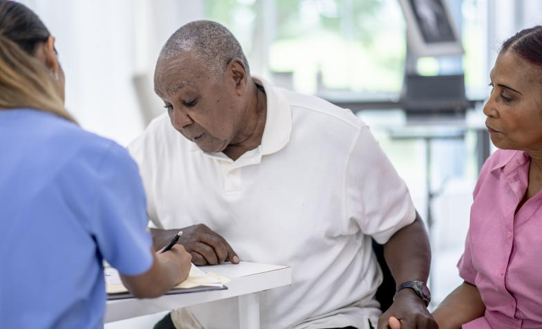 Elderly man looks at a piece of paper while holding his wife's hand