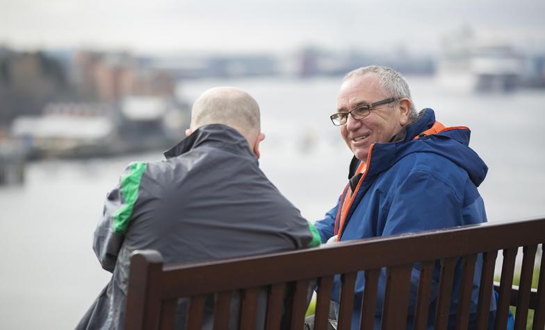 Two men talking on a bench
