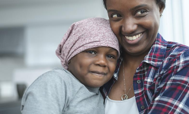 A mother hugs her daughter who is wearing a bandana