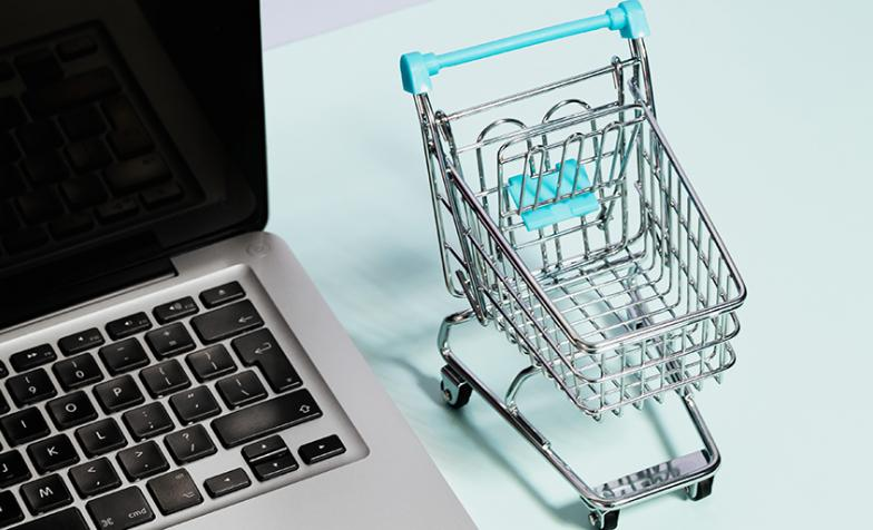A stock image of a small shopping trolley next to a laptop