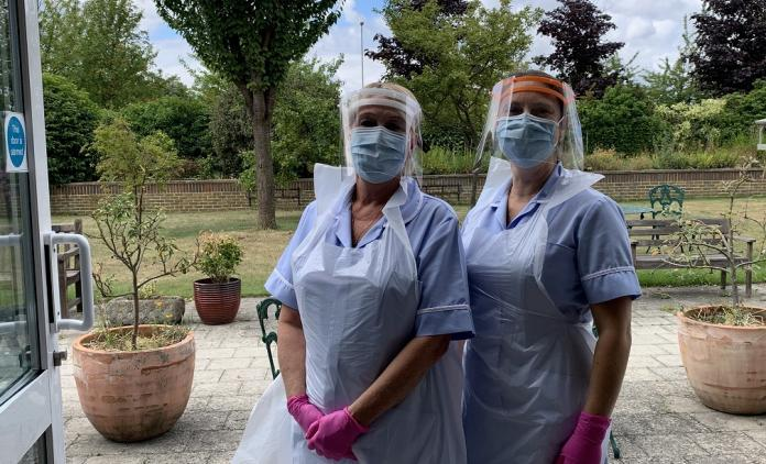 Two nurses in full PPE outside a building