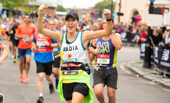 Female runner cheering in Hospice UK vest
