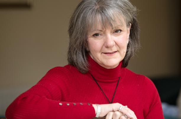 Carole Walford in red jumper, landscape headshot