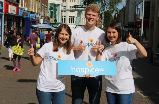 Hospice UK staff in Sutton High Street with thumbs up, zoomed out image