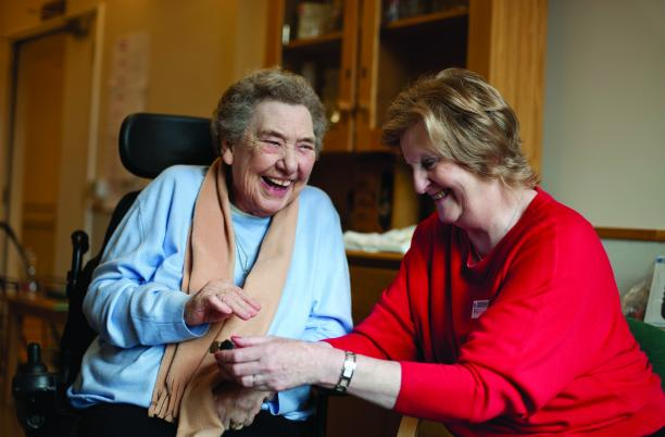 Older woman with in wheelchair with nurse