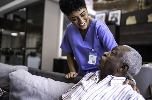 Hospice care photo, nurse smiling at elderly patient sitting on a sofa