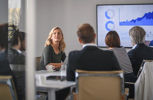 Stock photo of a group of men and women, seated, having a board meeting