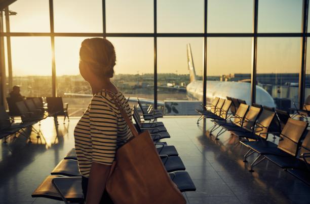 woman walking through airport looking through window