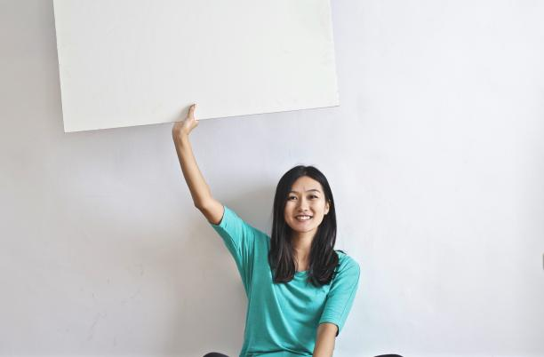 Stock photo of smiling woman holding up a blank poster
