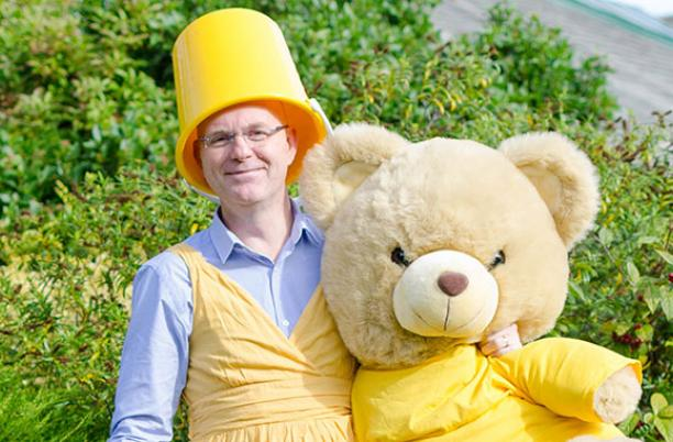 Going yellow at Wirral Hospice, a man with a yellow bucked on his head holding a yellow bear