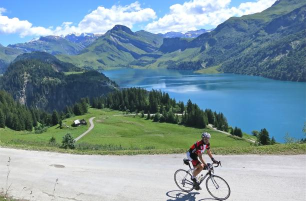 Geneva to Nice Cycle event participant with lake and mountain views