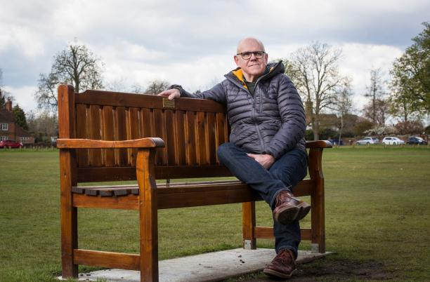David sitting on a bench dedicated to his father