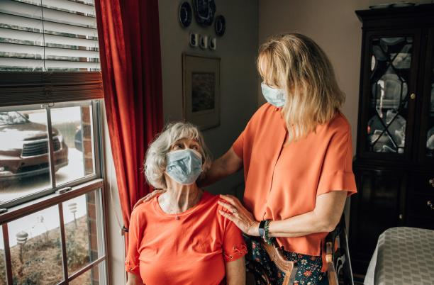 Daughter talking with her mother wearing protective mask