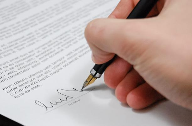 A stock photo of someone signing a legal document