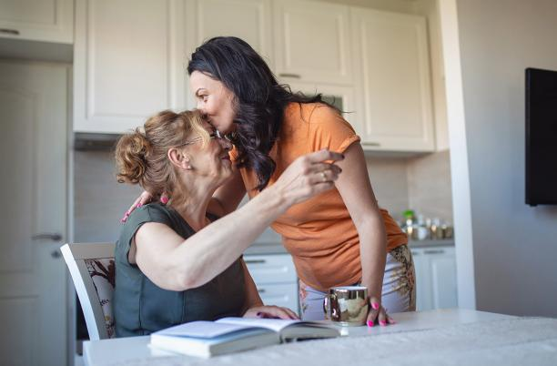 Woman kisses her mother on the forehead