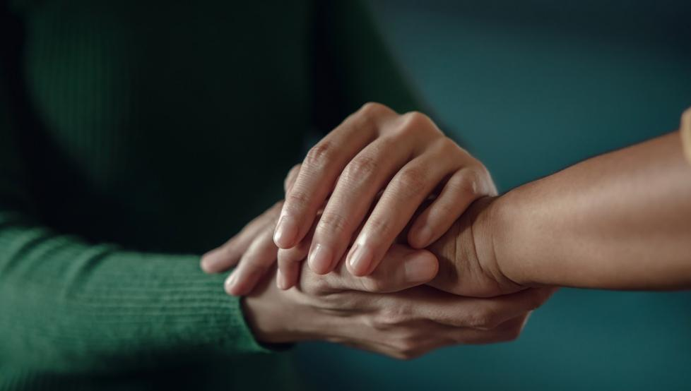 Stock photo of two people holding hands supportively