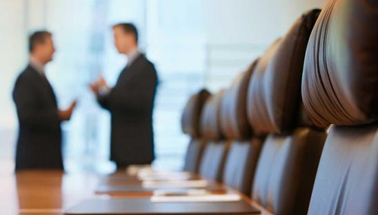 Stock photo of two people talking in the distance, in a boardroom with a table and chairs