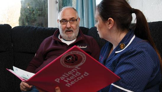 Man discussing and looking at health record with nurse
