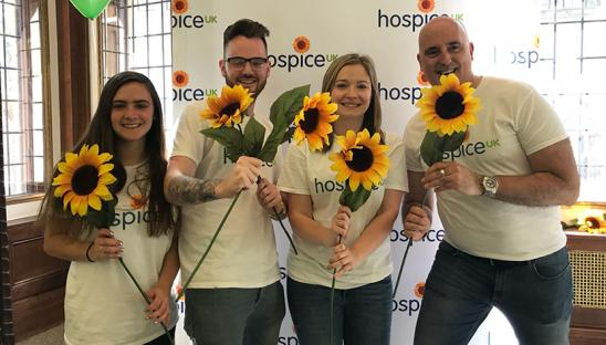 James with the team awaiting runners at the 2019 London Marathon holding sunflowers