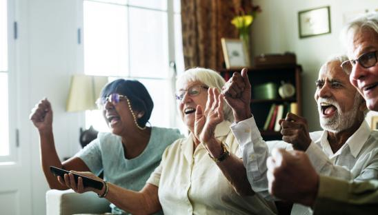 Older people sitting together on a sofa and cheering