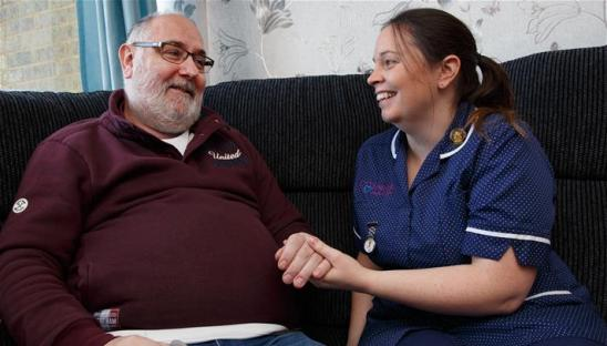 A photo of someone receiving home care by a hospice nurse