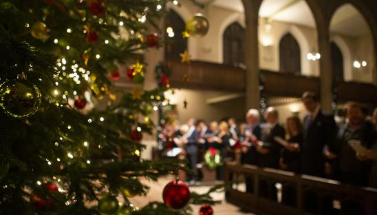 A photo through the Christmas tree at the 2019 Hospice UK Christmas Carol Service