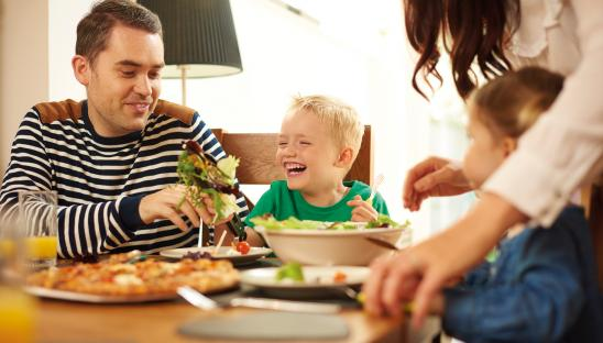 A stock photo of a young child enjoying a family meal with their father