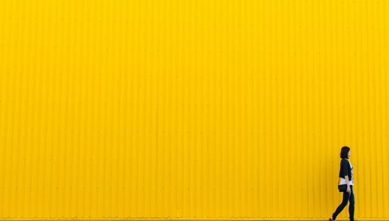 A stock image of a woman walking past a yellow background